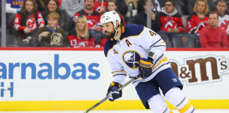 Zach Bogosian skates by a section of onlooking Devils fans.