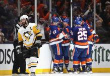 Star of Pittsburgh Penguins Defence, Kris Letang, skates away as New York Islanders celebrate a goal in Game 2.