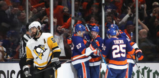 Star of Pittsburgh Penguins Defence, Kris Letang, skates away as New York Islanders celebrate a goal in Game 2.