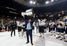 Craig Berube lifts the Cup, the St. Louis Blues cheering behind him.