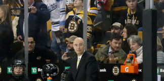 Pierre McGuire watches the Boston Bruins warm up.