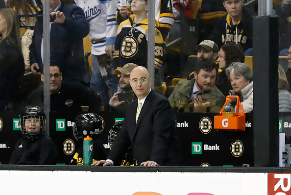 Pierre McGuire watches the Boston Bruins warm up.