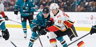 Mikael Backlund skates the puck in a Calgary Flames vs San Jose Sharks matchup.