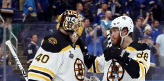 Tuukka Rask #40 and David Pastrnak #88 of the Boston Bruins