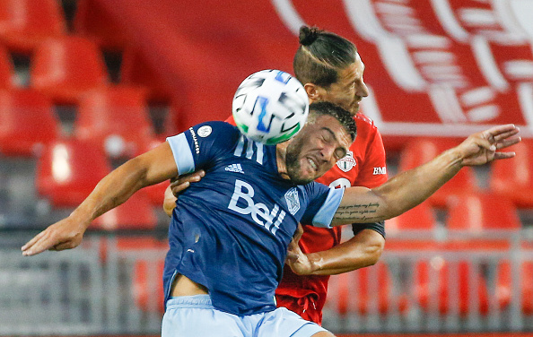 Vancouver Whitecaps FC player Lucas Cavallini battles with Toronto FC player Omar Gonzelez for a header at BMO Field