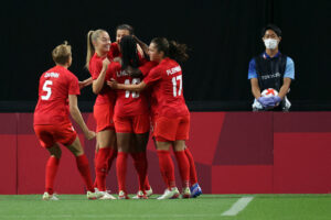 CanWNT player Christine Sinclair celebrates with teammates after scoring at Sapporo Dome