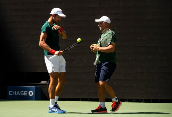 Novak Djokovic, who is attempting to complete the Calendar Grand Slam, consults with his coach.